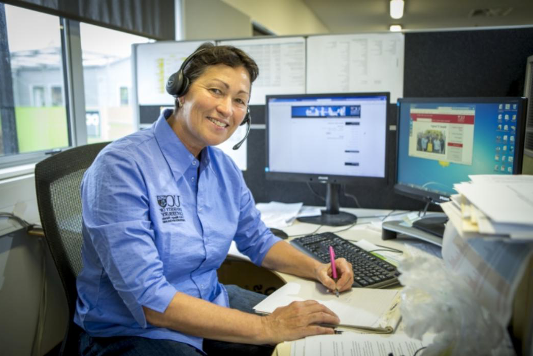Smiling lady from the IT Service Desk with her headset mic on ready to help