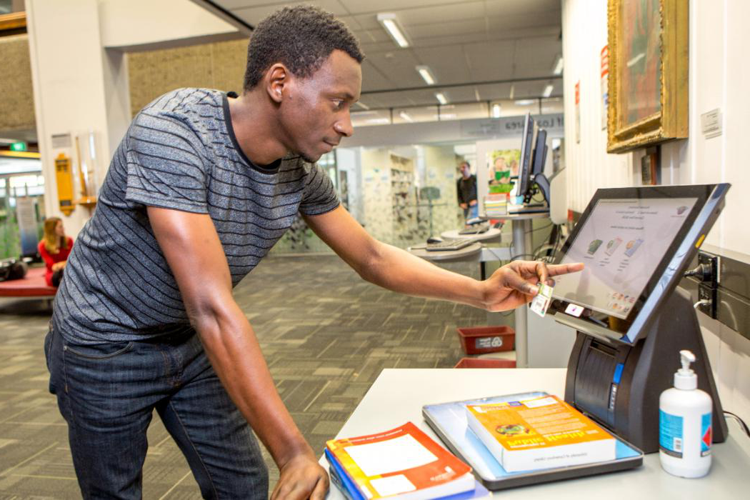 male students checking out books in library