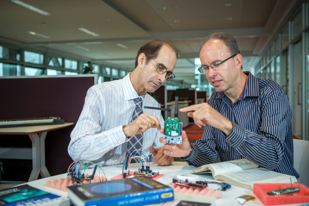 Two researchers looking at a circuit board